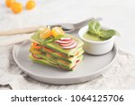 Stock photo raw zucchini lasagna with vegetables and pesto sauce light background vegetarian raw diet concept 1064125706