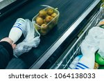 man put products on cash line... | Shutterstock . vector #1064138033