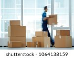 Small photo of Blurred motion of contemporary worker with packed box walking to new office while delivering it to client