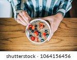 crop woman close up eating oat... | Shutterstock . vector #1064156456