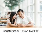 happy asian couple using... | Shutterstock . vector #1064160149