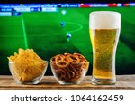 glass of beer and snack on a... | Shutterstock . vector #1064162459