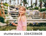 funny kid girl playing mini... | Shutterstock . vector #1064208608