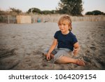 funny kid boy resting on sand... | Shutterstock . vector #1064209154