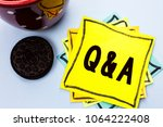 Small photo of Writing note showing Q A. Business photo showcasing Ask Frequently Faq Asked Question Help Solving Doubt Query Support written on Yellow Sticky Note Paper on the plain background Cup.
