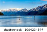 Fishing Boat heading up Pitt Lake with the Snow Capped Peaks of the Golden Ears, Tingle Peak and other Mountain Peaks of the Coast Mountain Range in the Fraser Valley of British Columbia, Canada