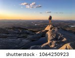 young man standing on mountain... | Shutterstock . vector #1064250923