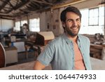 smiling young woodworker with a ... | Shutterstock . vector #1064474933