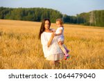 mom and daughter walking in the ... | Shutterstock . vector #1064479040