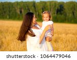 mom and daughter walking in the ... | Shutterstock . vector #1064479046