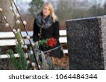 woman in cemetery sits at a... | Shutterstock . vector #1064484344
