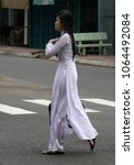 Small photo of Chau Doc, Vietnam, November 3rd 2012. A final year girl student walking confidently to school wearing the elegant white school outfit called ao dai.
