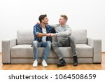 the two happy men on the sofa... | Shutterstock . vector #1064508659