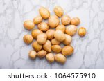 heap of young unpeeled potatoes ... | Shutterstock . vector #1064575910