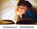 a happy smiling boy lies in bed ... | Shutterstock . vector #1064584646