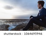 pensive man in suit sits on the ... | Shutterstock . vector #1064695946