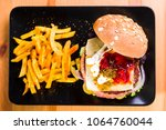 Small photo of Hamburger with cheese and pickles served on a black plate and accompanying potatoes
