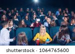 cinema hall full of young... | Shutterstock . vector #1064765600