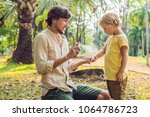 dad and son use mosquito spray... | Shutterstock . vector #1064786723