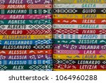 Small photo of Colorful bracelets with names, a typical italian souvenir. useful as a pattern or background for baby name choice concept.