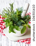 Spicy herbs in white ceramic mortar and pestle. - stock photo
