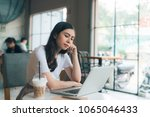 woman sadly looking at laptop... | Shutterstock . vector #1065046433