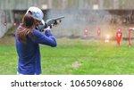 woman in practice shooting gun... | Shutterstock . vector #1065096806