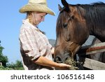 Young Cowgirl Feeding Horse In...