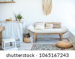 Beautiful spring photo of kitchen interior in light textured colors. Kitchen, living room with beige couch sofa, large cactus and woven macrame on the wall - stock photo