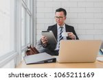 young asian businessman looking ... | Shutterstock . vector #1065211169