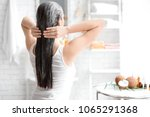 young woman applying oil onto...   Shutterstock . vector #1065291368
