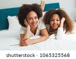 mother and daughter enjoying on ... | Shutterstock . vector #1065325568
