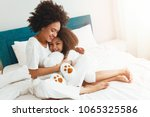 mother and daughter enjoying on ... | Shutterstock . vector #1065325586