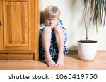 sad cute little blonde boy sits ... | Shutterstock . vector #1065419750