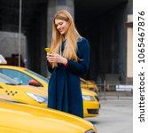 a young girl calls a taxi by... | Shutterstock . vector #1065467876