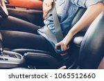 asian woman fastening seat belt ... | Shutterstock . vector #1065512660