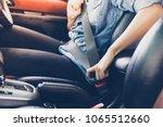 asian woman fastening seat belt ... | Shutterstock . vector #1065512660