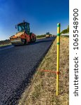 Small photo of Guide rail. Road roller rolls freshly laid asphalt. Road construction.