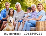 Stock photo three generation family sitting with pet dog in the garden 1065549296