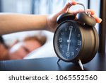 woman in bed turns off a retro... | Shutterstock . vector #1065552560