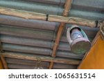 Small photo of Saraburi Thailand-APR 10-2018;An old lamp hanging on a nail attached to a wooden rafter of a roof at outdoor Kitchen Nopparat