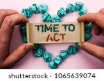 Small photo of Word writing text Time To Act. Business concept for Action Moment Strategy Deadline Perform Start Effort Acting written on Cardboard Paper Holding by man plain background on Heart Paper Balls.
