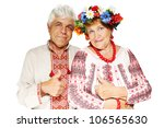 Mature couple in Ukrainian costumes show a gesture of ok - stock photo