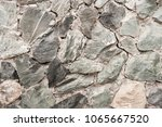 Small photo of Close-up wall of uneven rough uncouth gray stones.