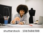 Small photo of Smiling African American fashion illustrator sketching or drawing at workplace. Portrait of attractive curly female working in modern atelier. Freelance.