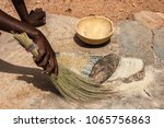 Small photo of An african woman using her fiber broom after having ground cereals (millet/sorghum) in Burkina Faso. Tools : grindstones, fiber broom, calebash.