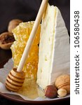 Delicious cheese, nuts and honeycombs on a ceramic plate. - stock photo