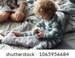 Small photo of little curly toddler baby boy sitting on the bed and holding his favorite toy