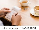 Small photo of Hands hold the bills to check the coffee price with coins tip on the table