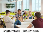 Stock photo happy multiethnic group of high school students chatting while taking lunch at school cafeteria 1066245839